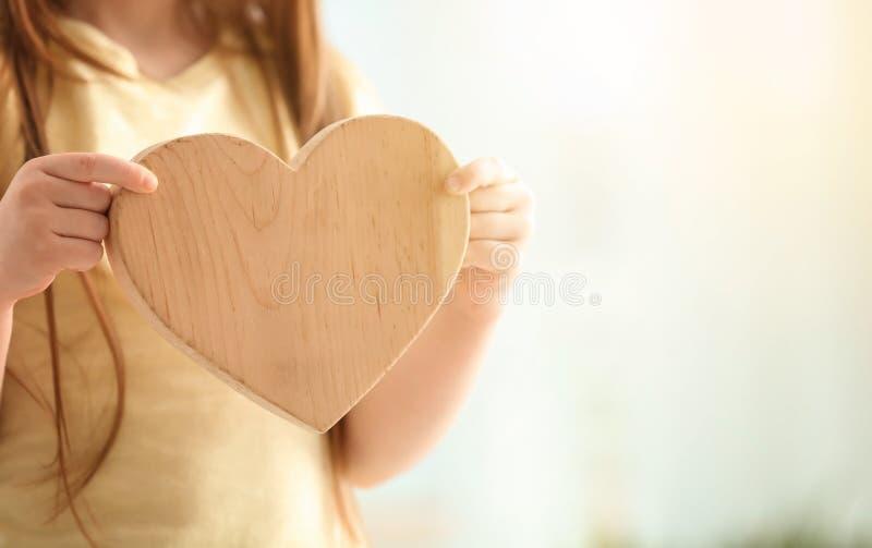 Nettes kleines Mädchen mit hölzernem Herzen auf hellem Hintergrund, Nahaufnahme stockbilder