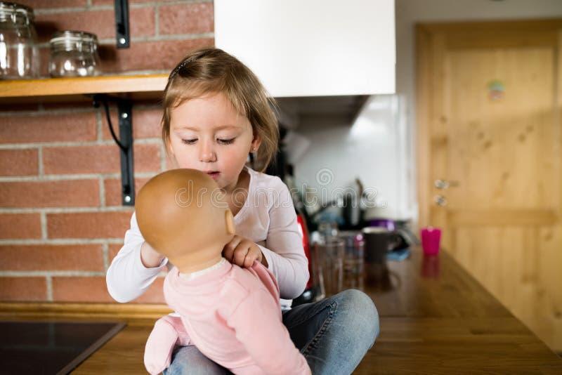 Nettes kleines Mädchen mit ihrer Puppe, die auf Küche Countertop sitzt lizenzfreies stockfoto