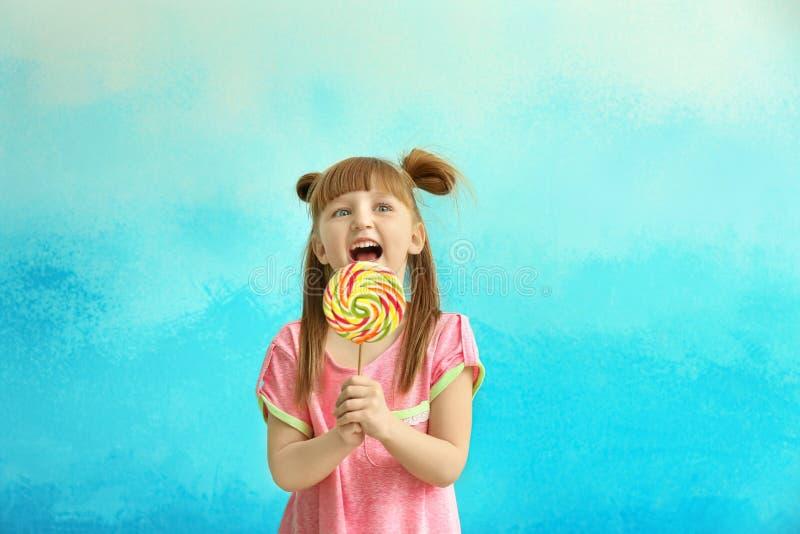 Nettes kleines Mädchen mit Lutscher auf Farbhintergrund stockbild