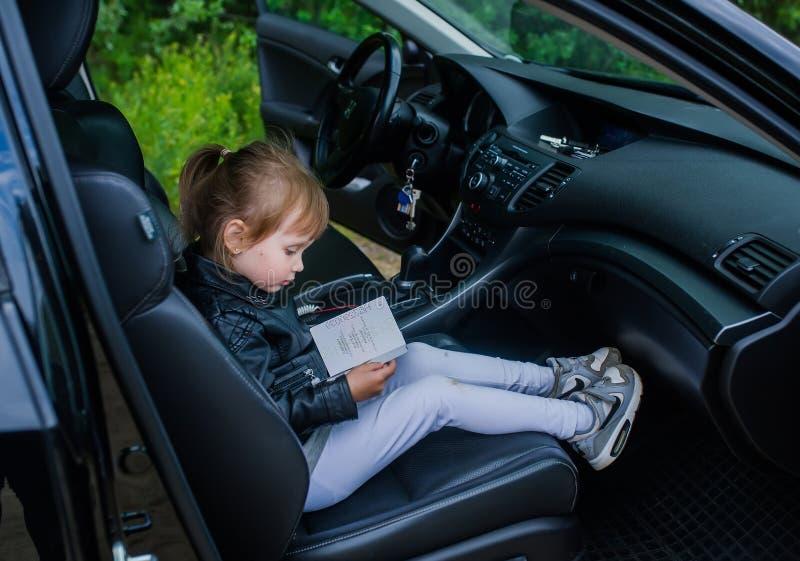 Nettes kleines Mädchen mit Pass sitzen in einem Autositz, der zu einer Fahrt mit Eltern bereit ist lizenzfreie stockfotos