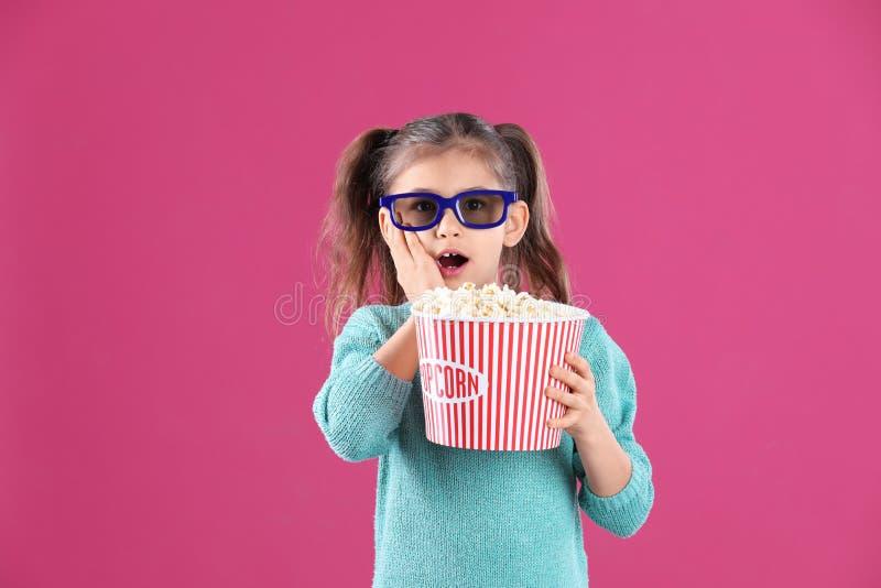 Nettes kleines Mädchen mit Popcorn und Gläsern lizenzfreie stockbilder