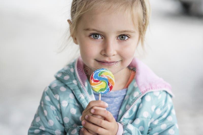 Nettes kleines Mädchen mit Süßigkeit stockfotografie