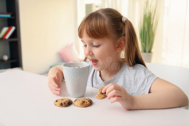 Nettes kleines Mädchen mit Schale heißem Kakaogetränk und -plätzchen zu Hause lizenzfreie stockfotos