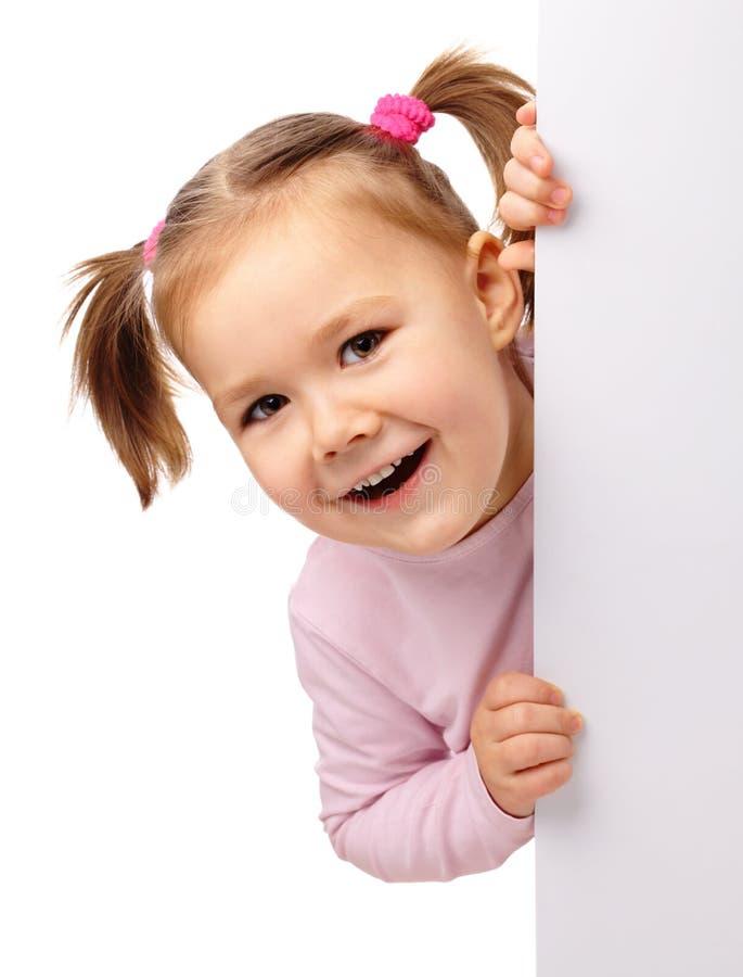 Nettes kleines Mädchen mit unbelegtem Vorstand stockfotografie
