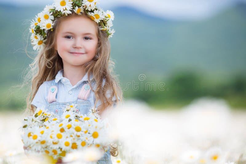 Nettes kleines Mädchen mit weißen Gänseblümchen des gelben Eimers lizenzfreie stockbilder