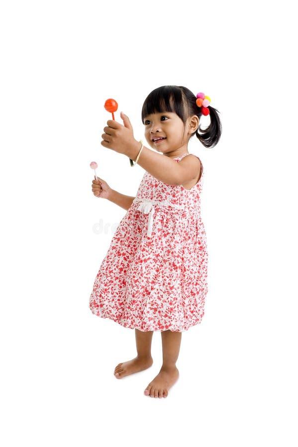 Nettes kleines Mädchen mit zwei Lutschern stockfotos