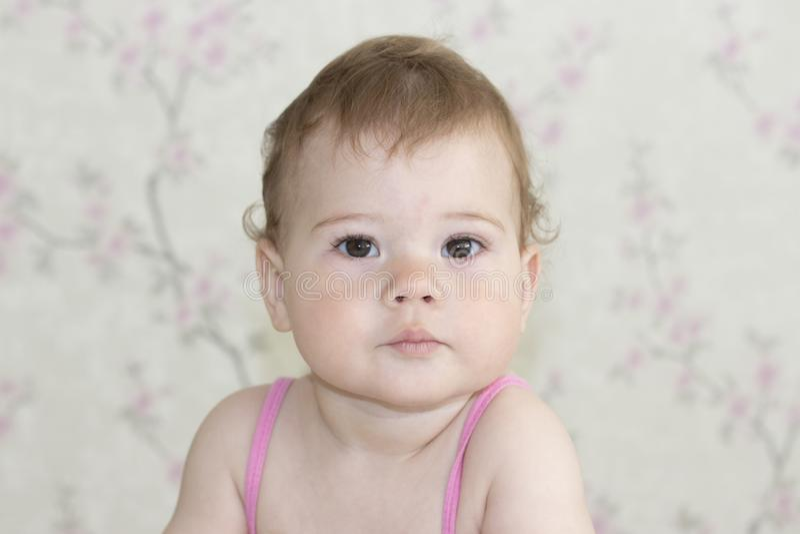 Nettes kleines Mädchen 10 Monate alte, Babyporträtnahaufnahme Das Baby betrachtet die Kamera mit einem ernsten Gesicht, Baby mit stockbilder