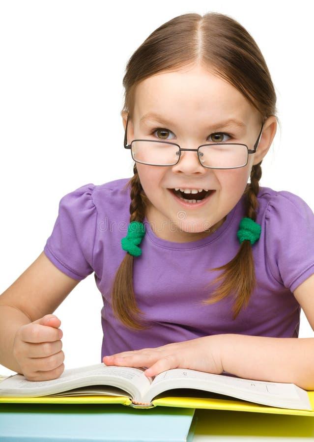 Nettes kleines Mädchen schlägt ein Buch mit der Faust lizenzfreies stockbild