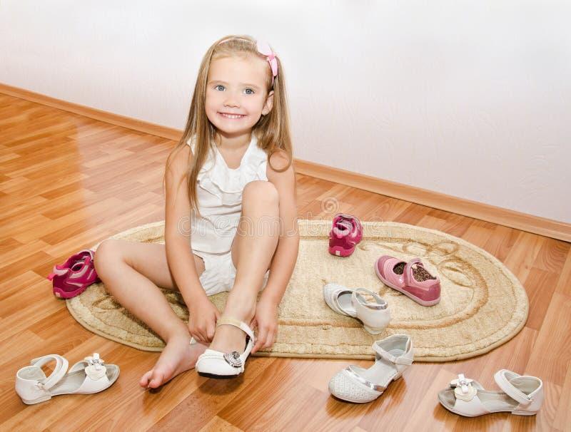 Nettes kleines Mädchen setzt ihre Schuhe lizenzfreies stockbild
