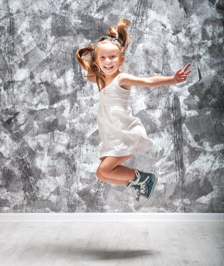 Nettes kleines Mädchen springen lizenzfreie stockfotografie