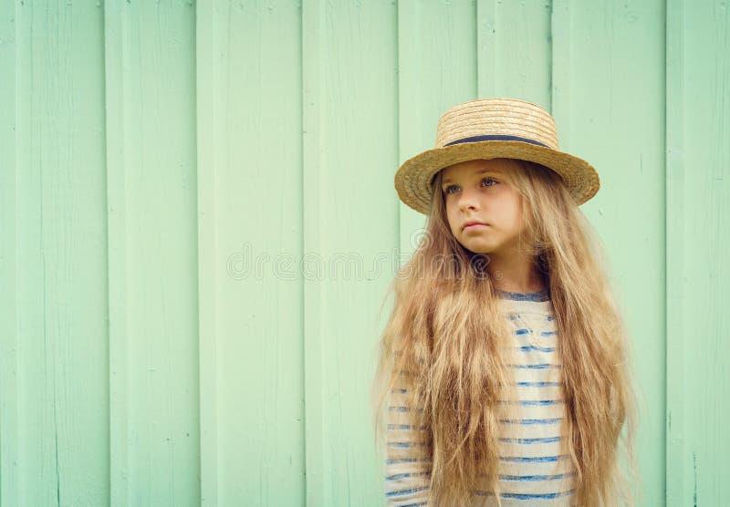 Nettes kleines Mädchen steht nahe einer Türkiswand im Kreissägenhut und schaut nachdenklich beiseite Raum für Text stockfotos