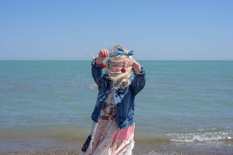 Nettes kleines Mädchen am Strand an einem windigen Tag stockfotografie