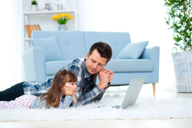 Nettes kleines Mädchen, Tochter, Schwester und junger Vativater oder Bruderblick auf den Laptopmonitorcomputer, liegend auf Teppi stockfoto