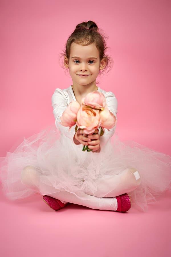Nettes kleines Mädchen in Tulle-Rock mit einem Blumenstrauß von Blumen auf einem rosa Hintergrund lizenzfreies stockbild
