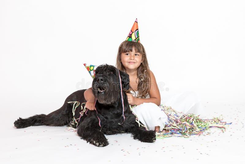 Nettes kleines Mädchen umfasst schwarzen Hund auf dem Weiß stockfotos