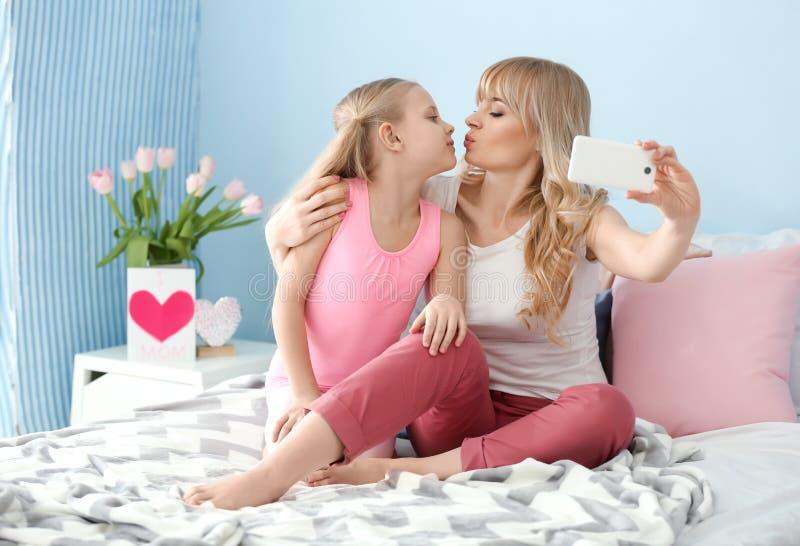Nettes kleines Mädchen und ihre Mutter, die selfie im Schlafzimmer nimmt lizenzfreies stockfoto