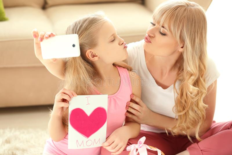 Nettes kleines Mädchen und ihre Mutter, die zu Hause selfie mit handgemachter Karte nimmt lizenzfreies stockfoto