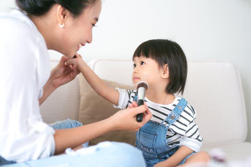 Nettes kleines Mädchen und ihre schöne Mutter tun Make-up während lizenzfreie stockfotografie