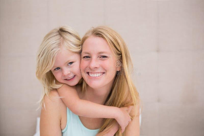 Nettes kleines Mädchen und Mutter auf Bett lizenzfreies stockfoto