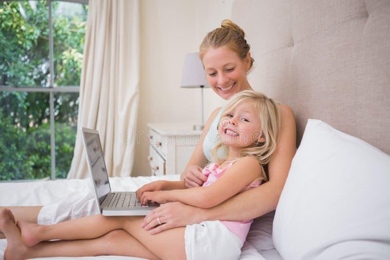 Nettes kleines Mädchen und Mutter auf Bett unter Verwendung des Laptops lizenzfreies stockbild