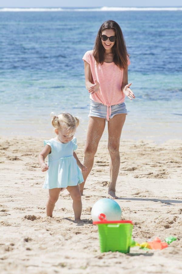 Nettes kleines Mädchen, welches das blaue Kleid spielt Wasserball mit ihr trägt lizenzfreie stockfotografie