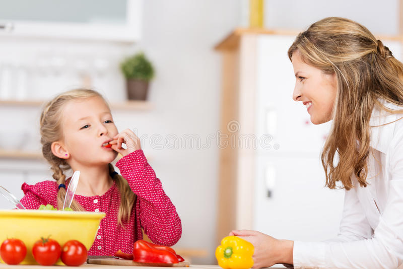 Nettes kleines Mädchen, welches das Gemüse schmeckt lizenzfreie stockfotografie