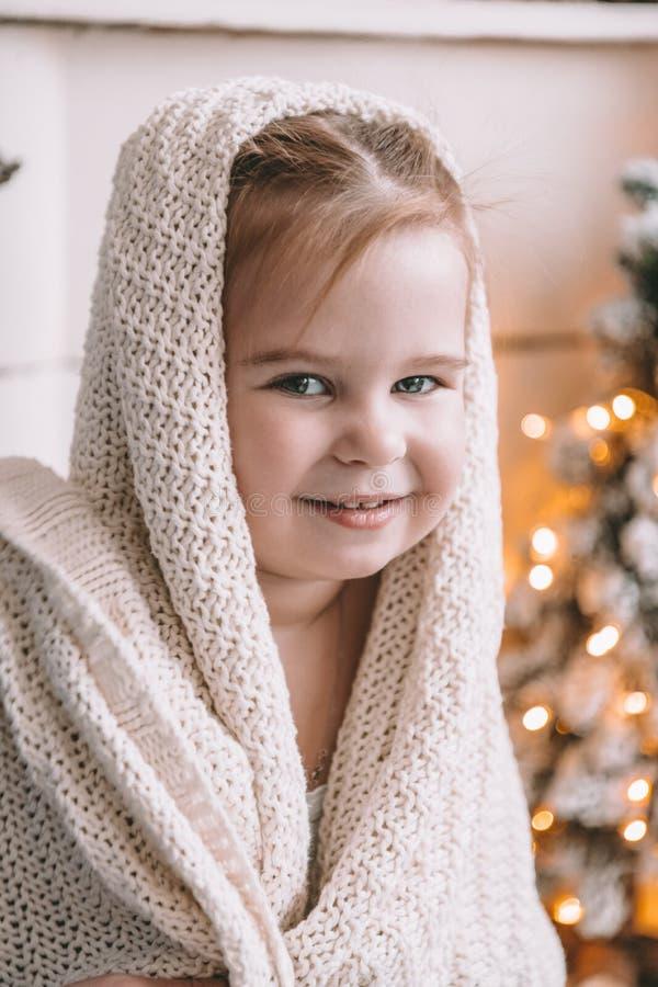 Nettes kleines Mädchen zu Hause bedeckt in einem großen Plaid oder in einem Schal lizenzfreies stockfoto