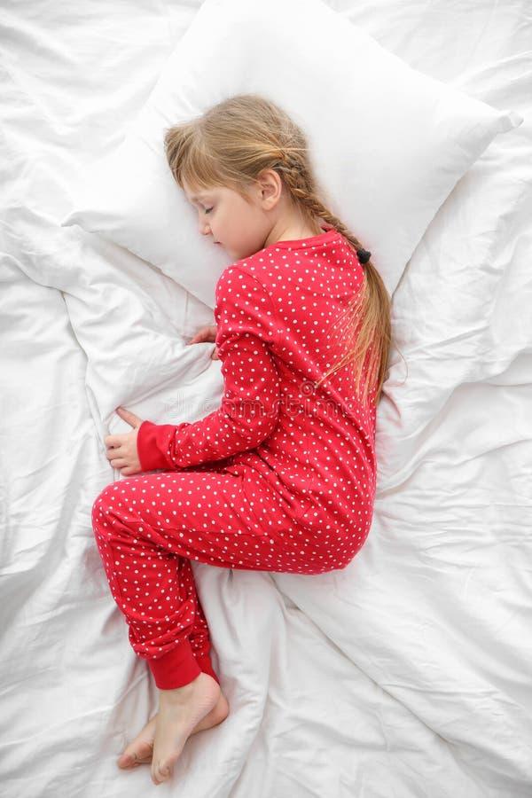 Nettes kleines M?dchen, das im Bett, Draufsicht schl?ft stockfoto