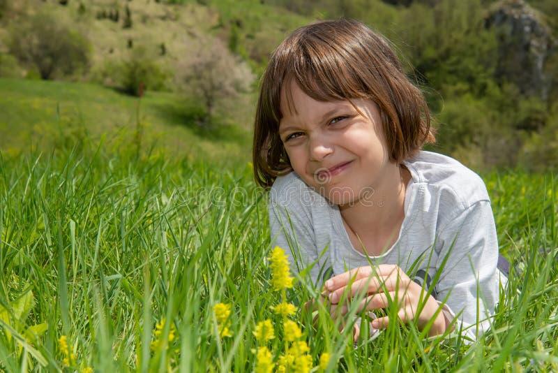 Nettes kleines M?dchen, das im Gras und im Lachen liegt lizenzfreies stockbild