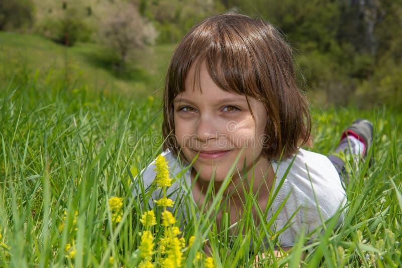Nettes kleines M?dchen, das im Gras und im Lachen liegt lizenzfreies stockfoto