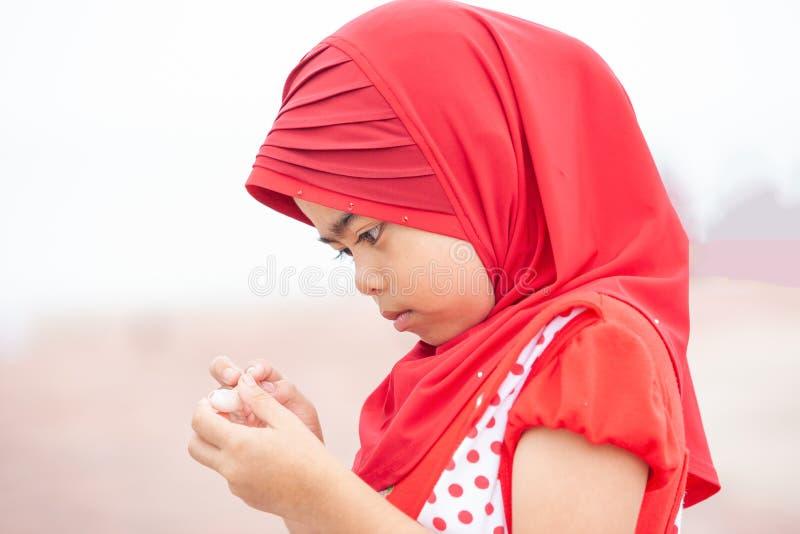Nettes kleines moslemisches Mädchen in der traditionellen Kleidung, im roten hijab oder in Ni stockfotografie