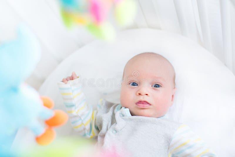 Nettes kleines neugeborenes Baby in der Krippe mit bunten Spielwaren stockfotografie