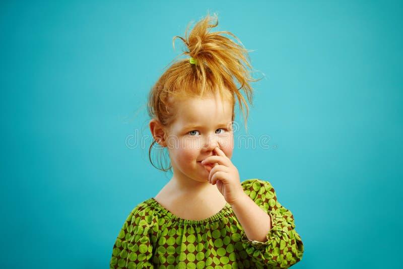 Nettes kleines Rothaarigemädchen wählt ihre Nase mit dem Finger auf dem lokalisierten Blau aus lizenzfreies stockbild
