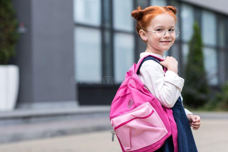 nettes kleines Rothaarigeschulmädchen in den Brillen, die Rucksack und das Lächeln halten stockbild