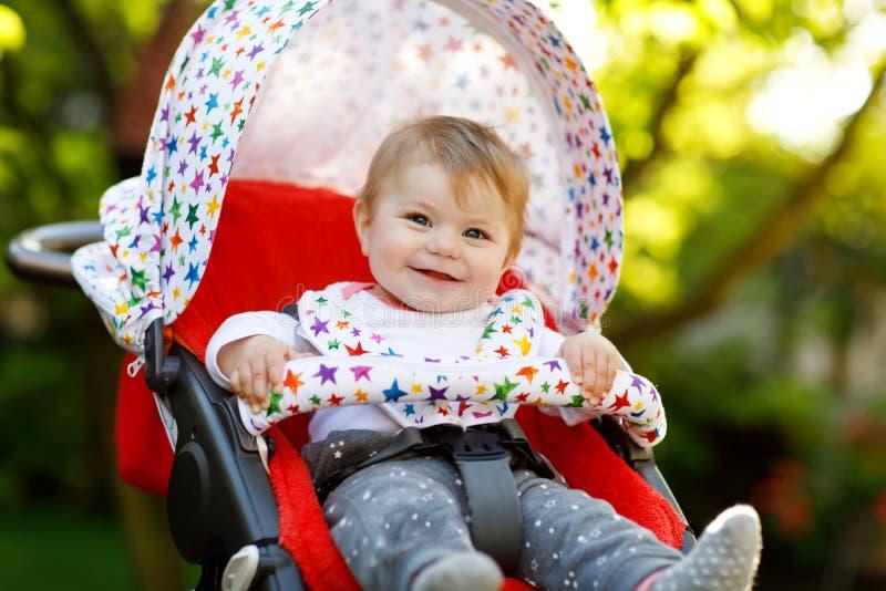 Nettes kleines schönes Baby von 6 Monaten, die in der Pram- oder Spaziergänger- und Warten Mutter sitzen lizenzfreie stockbilder