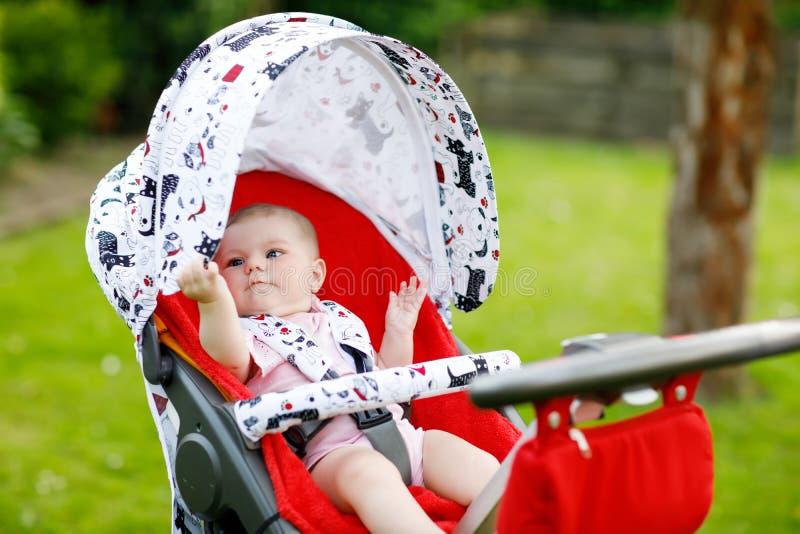 Nettes kleines schönes Baby von 6 Monaten, die in der Pram- oder Spaziergänger- und Warten Mutter sitzen lizenzfreies stockfoto