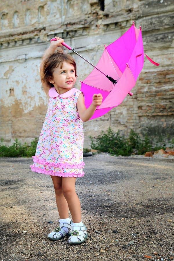 Nettes kleines schönes Mädchen mit rosa Regenschirm und Handtasche im Park lizenzfreies stockfoto