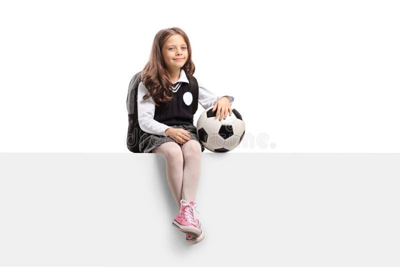 Nettes kleines Schulmädchen mit einem Fußball, der auf einer Platte sitzt lizenzfreies stockbild