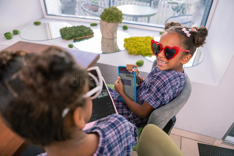 Nettes kleines strahlendes Mädchen, welches die rote Herz-förmige Sonnenbrille hält Tablette trägt lizenzfreies stockfoto