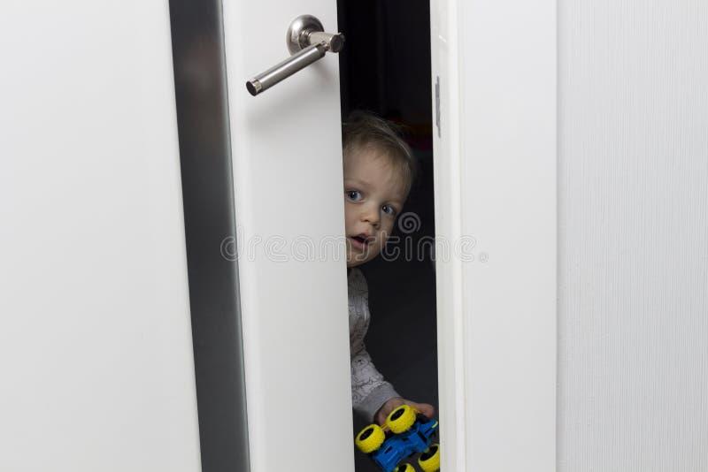 Nettes Kleinkind, das heraus von hinten die angelehnte Tür schaut stockbild