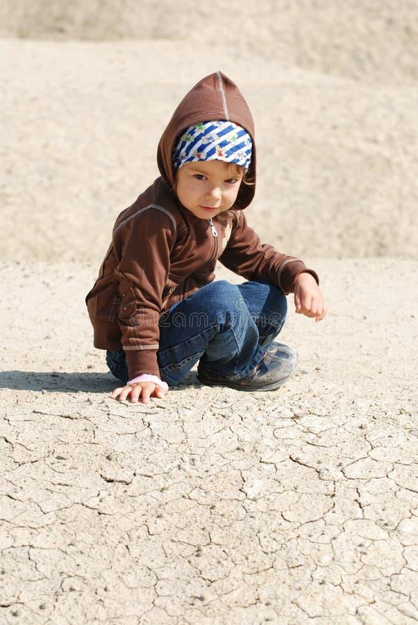 Nettes Kleinkind, das im Schmutz spielt stockfotos