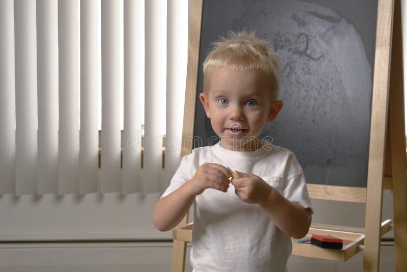 Nettes Kleinkind des kleinen Jungen, zwei Jahre alt Zeichnen auf das chalkbo stockfotografie