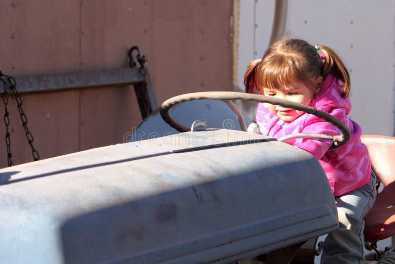 Nettes Kleinkind-Mädchen, das auf Traktor spielt stockfotografie