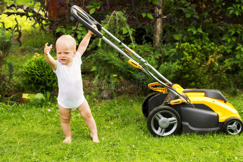 Nettes Kleinkind mit einem Rasenmäherausschnittgras stockbilder