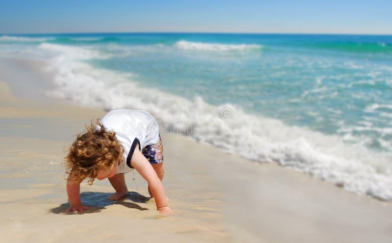 Nettes Kleinkind-Schätzchen auf Strand stockbild