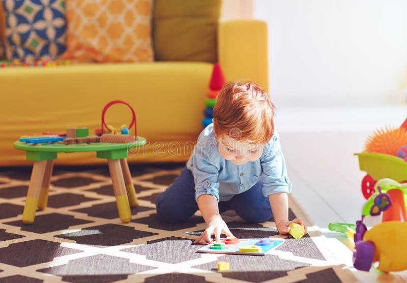 Nettes Kleinkindbaby, das zu Hause mit Spielwaren auf dem Teppich spielt stockfotos