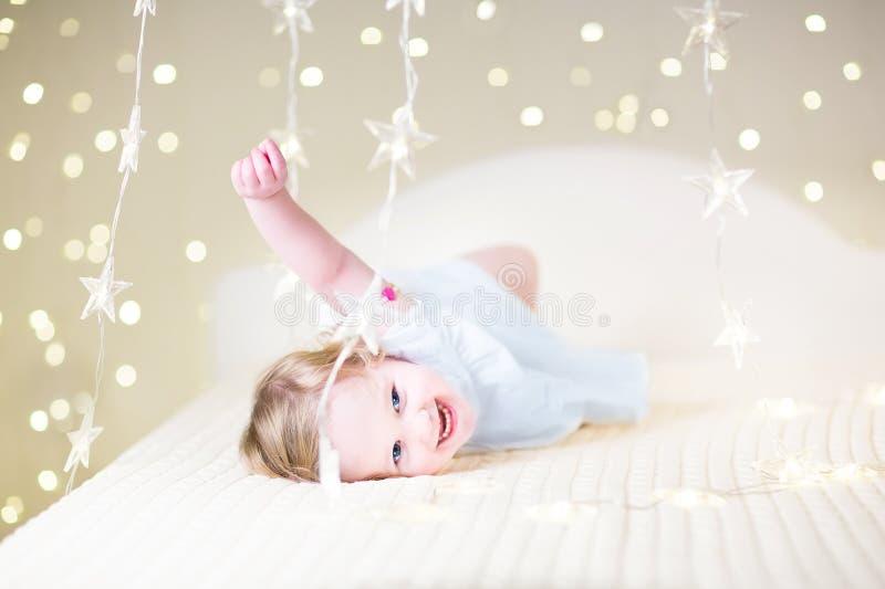 Nettes Kleinkindmädchen, das auf einem Bett zwischen warmem weichem Weihnachten L spielt stockbild