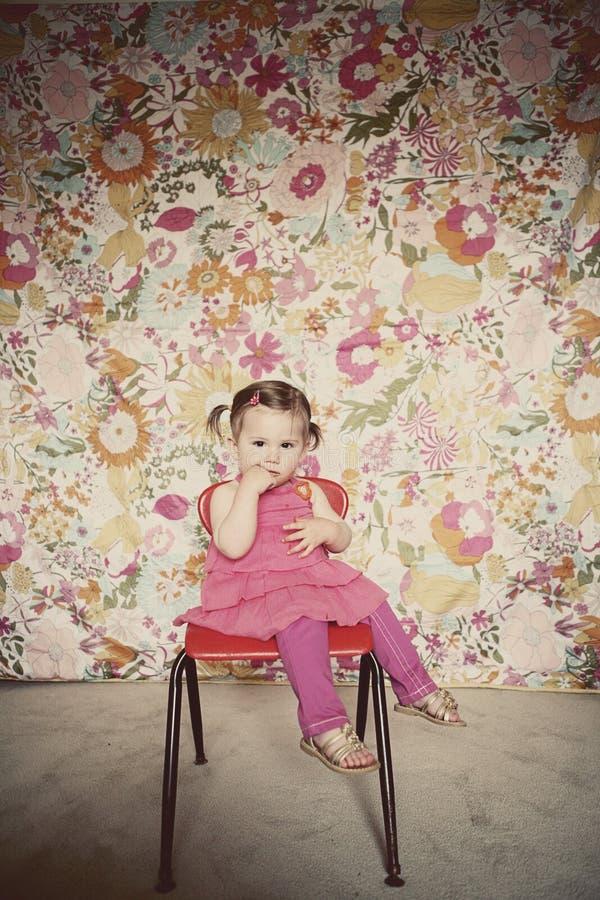 Nettes Kleinkindmädchen, das auf einem roten Stuhl sitzt stockbild