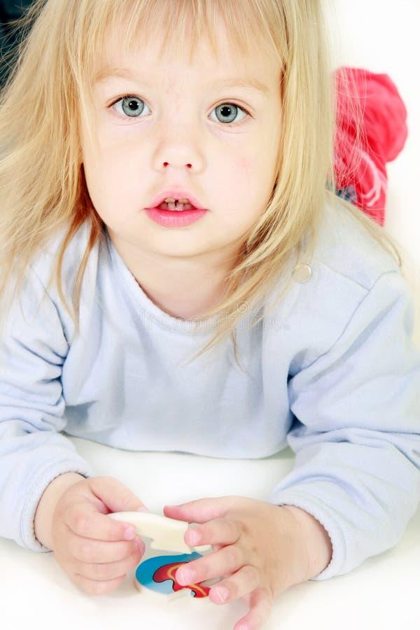 Nettes Kleinkindmädchen, das in der Kamera schaut stockfotografie