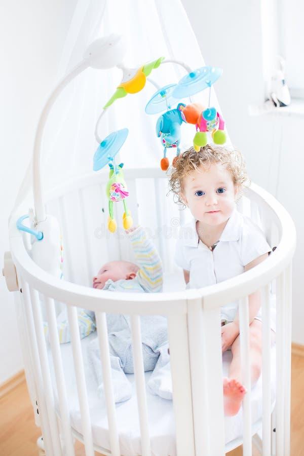 Nettes Kleinkindmädchen, das in der Krippe des neugeborenen Bruders sitzt stockbild